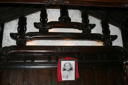 One of the founders of Tan Ky house, below the typically Japanese roof supports.