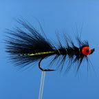 Ogonek – czarny marabut, mirror flash. Tułów – czarny marabut. Jeżynka na tułowiu – czarna kura Owijka – złoty drut. Oczka – pomarańczowe koraliki.