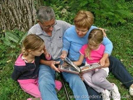 grandfather-grandmother-grandchildren-look-at-photo-album
