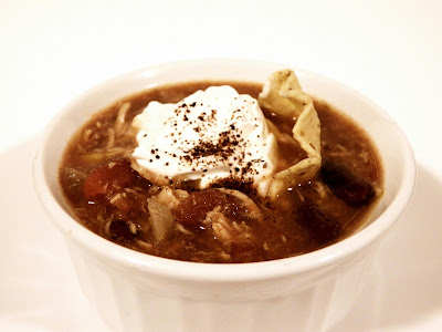 Slow cooker chicken tortilla soup - garnished with sour cream, a tortilla chip, and a sprinkle of chili powder