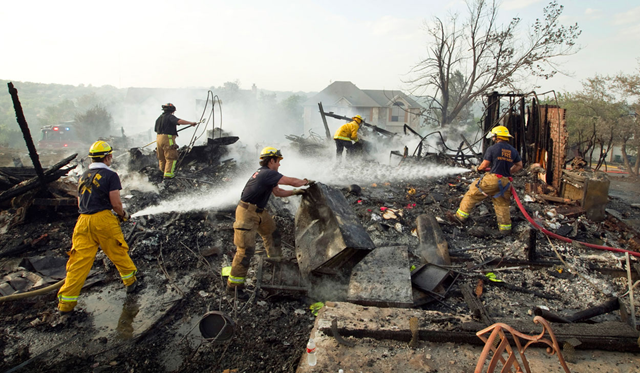 Austin firefighters work at a house that burned to the ground on Callbram Lane in the Oak Hill neighborhood in Austin on Sunday, April 17, 2011. The wildfire destroyed or damaged 21 homes and involved more than 100 acres. Jay Janner / statesman.com