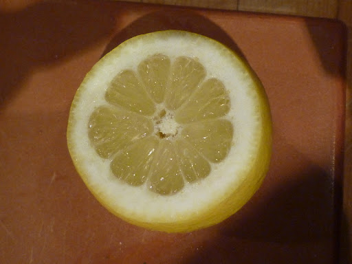 Lemon trimmed to reveal fruit under the skin.