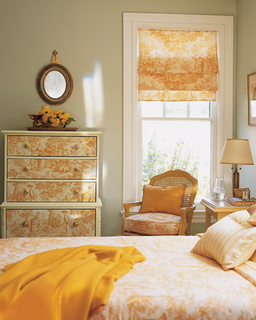Drawer fronts covered in a sunny yellow toile fabric look distinctive. For a project like this one, choose wooden drawers with easy-to-remove faces, such as those held together with nails or screws.