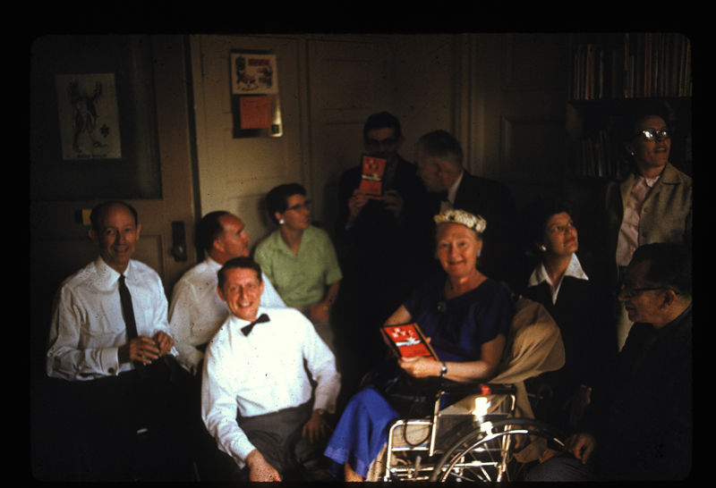 ONE Incorporated autograph party for Harry Otis (aka Shelton Dewey), author of The Keval. Includes W. Dorr Legg (far left), Hal Call (front with bowtie), Harry Otis (in white behind Call), Dr. Blanche Baker (in wheelchair), Del Martin (right with white collar), Phyllis Lyon (upper right) and other friends of ONE Incorporated. 1959.