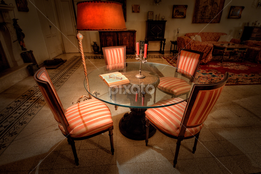 Chairs around a glass table by Anton Donev - Artistic Objects Furniture ( illuminated, reading, glasses, indoors, apartment, antiquities, furniture, heat, comfortable, candle, retro revival, ancient, seat, no people, living room, glass, electric light, obsolete, home interior, old-fashioned, table, chair, lighting equipment, domestic room, lamp, book, lifestyles )