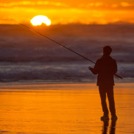 Sunset fishing at Karekare by John Lyon - Sports & Fitness Other Sports ( waves, silhouette, sunset, auckland, peace, hobby, ocean, fishing, sunrise, beach, surf )