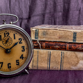 Vinatge alarm by Julian Popov - Artistic Objects Still Life ( alarm; book; textbook; paper; pocket; old; clock; dirty; classical; aged; decorated; hours; second; minutes; twelve; macro; engraved; mechanism; time; retro; design; antique; vintage; style; deadline; background; grunge; ornaments; detail; pattern; metal; countdown; knowledge; )