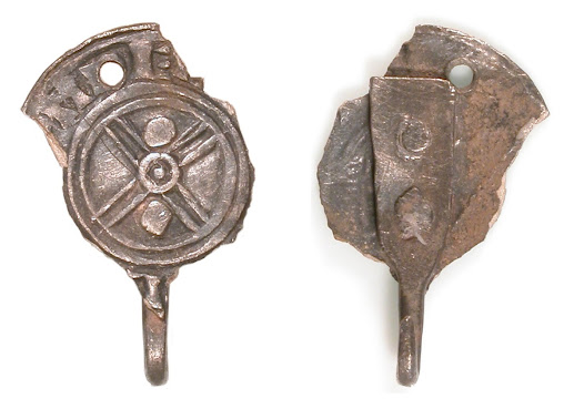 This unusual dress accessory, known as a hooked-tag, is made from a silver penny of King Cnut, like those in the Lenborough Hoard: the coin itself was struck in Derby. It seems to have been an 11th century fashion to make jewellery, mostly brooches, from coinage. This object was reported Treasure through the Portable Antiquities Scheme.