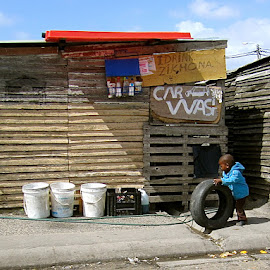 Boy playing with Tire in South African Township by Tyrell Heaton - Babies & Children Children Candids ( playing, township, south africa, langa, boy, tire )
