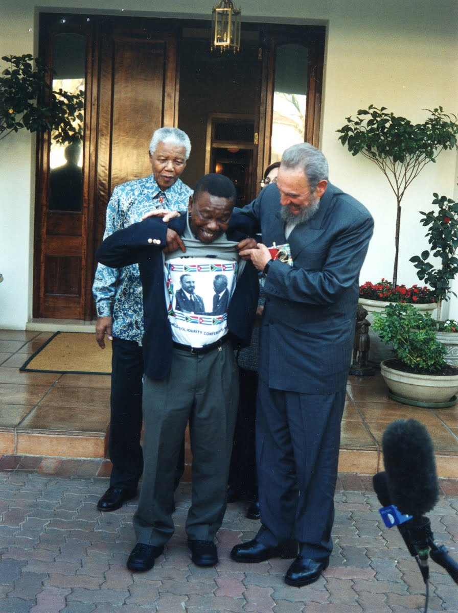 Nelson Mandela with a South African Communist Party leader Blade Nzimande lifts his shirt to show Cuban President Fidel Castro