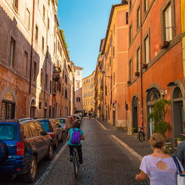 A Street in Rome by Bill Kuhn - City,  Street & Park  Street Scenes ( walking, rome, cars, woman, street, travel, bicyclist, italy, man, cobblestone, walkers, bicycle )