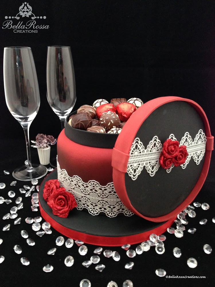 Be my Valentine!.... Chocolate Box cake. This cake was airbrushed with black ink and surrounded with sugar lace. The cake was finished with hand made gum paste roses embellished with edible glitter and a selection of chocolates on top - the perfect gift for a loved one on Valentine's Day!....