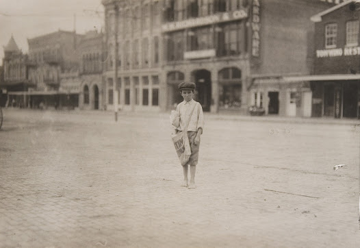 """""""Eleven year old newsie who has been selling for three years. He gets up at 2:30 A.M. Sundays, and at 5:00 A.M. school days. Makes about $1.25 a day. Norval Sharp. Photo taken early Sunday morning."""" — from Hine's field notes, 1913"""