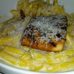 GF pasta in alfredo sauce topped with grilled salmon