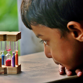 R for red, O for orange ...... by Anoop Namboothiri - Babies & Children Children Candids ( looking, toy, watching, colors, artistic, glass, anoop namboothiri, candid, hour glass, boy, daylight, closely )