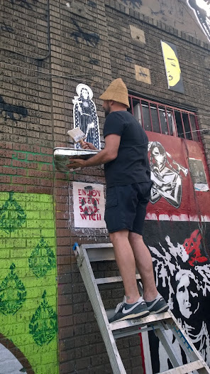 This is the curator of the Alley... pasting up some sent artwork.
