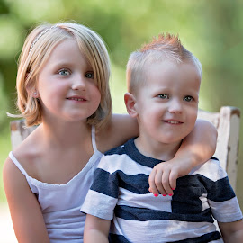 cousins by Carole Brown - Babies & Children Child Portraits ( sitting on a chair, blonde hair, hugging, greenery, blue eyes )