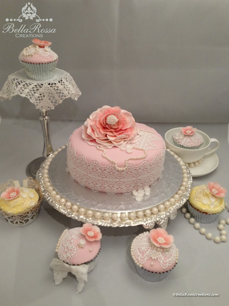 Vanilla sponge cake and cupcakes with caramel ganache. The cake was covered with dusty pink fondant and surrounded with sugar lace. The cake and cupcakes were also decorated with handcrafted gum paste flowers and necklace made from sugar pearls for that Vintage look.