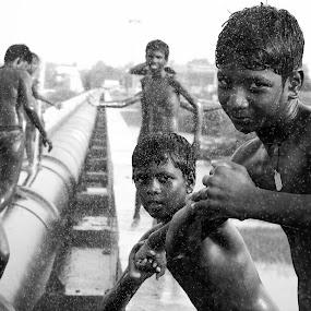 HOLIDAY by Gobinath S K - Black & White Portraits & People ( playing, seashore, raining, boys, children, india, roadside, people, rain, portrait, black, , Urban, City, Lifestyle )