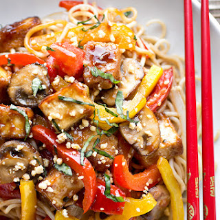 Thai-Style Crispy Tofu Sauteed with Red and Yellow Bell Peppers, Onions, Mushrooms and Tomatoes with Fresh Basil and Crushed Peanuts Over Brown Rice Noodles