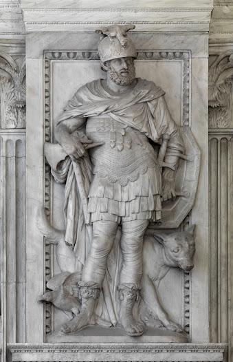 Mars is de meest vereerde god van het Romeinse Rijk. Je ziet de bebaarde Mars in volle wapenuitrusting leunend op een fikse bijl en als enige van de goden in dit gebouw in een broek gekleed. Met zijn linkerarm draagt hij een schild en toont een zwaard. Tot aan zijn voeten draagt hij een lagen mantel en zijn helm is getooid met een draak. In deze uitrusting is Mars overduidelijk de god van de oorlog, die zweert bij de strijd. De wolf naast Mars staat symbool voor de bloeddorstigheid van diegenen die oorlog voeren. De wolf verwijst daarnaast naar het oude Rome, waarmee Amsterdam zich in de zeventiende eeuw graag vergelijkt.