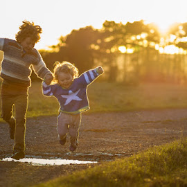 boys jumping over puddles by Keren Woodgyer - Babies & Children Children Candids ( photograph, jumping, blond, children, people, sun, caucasian, child, love, curly, autumn, family, happy, path, toddler, hair, smiling, footsteps, brothers, affection, pathway, grass, togetherness, behind, fun, dusk, sunset, sibling, outdoors, sunflare, trees, puddle, boy, holding hands )