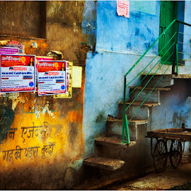 done for the day by Maricha Knight van Heerden - City,  Street & Park  Neighborhoods ( home, trolley, a simple life, blue wall, peaceful amid chaos, parked, green door, wall art, delivery trolley, yellow and blue, india, stariway, atmospheric, evening,  )