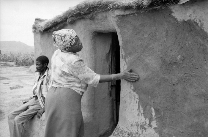 Woman plastering walls with mud. Daggakraal was an area deemed a 'black spot' by the apartheid government and was threatened with forced removal. Maintaining the home was seen as resistance to removal.