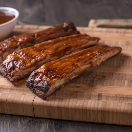 RIbs on a cutting board with BBQ sauce by Philip Stridh - Food & Drink Meats & Cheeses ( grill, beef, barbecued, pepper, rack, smoked, cooked, american, bones, meat, lunch, bbq, roasted, grilled, meal, spicy, delicious, roast, tangy, sauce, dinner, smokey, tasty, rib, ribs, sloppy, food, pork, tender, barbeque, summer, eat, barbecue, spareribs, picnic )
