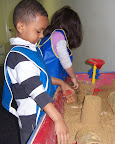 Child building with wet sand in sensory table
