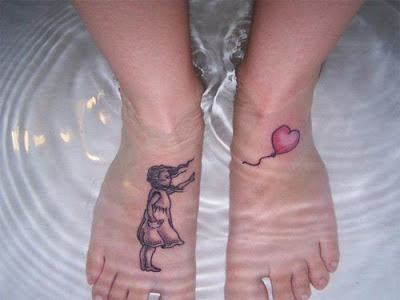 two feet in a tub of water, each foot is tattooed - the right foot has a grayscale rendering of a windblown little girl in Edwardian dress looking towards the left foot with her hand outstretched, the left foot has a red heart-shaped balloon appearing to float higher than the girl could reach