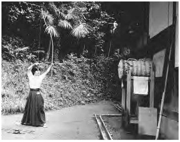 A young woman aims at a barrel of straw to practice the style of her archery, at the Tsurugaoka Hachiman Grand Shrine in Kamakura, Japan, 1986.