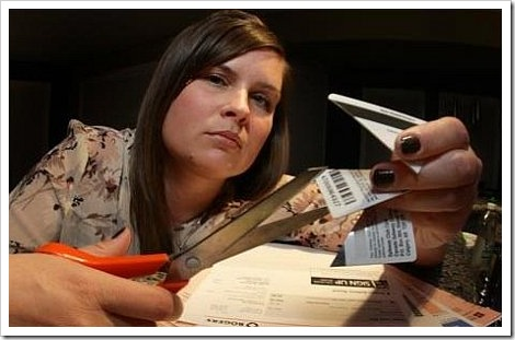 Bad credit repair - Woman cutting credit card with scissors.
