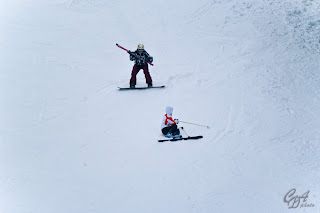 Snowboarder helping a fallen skier