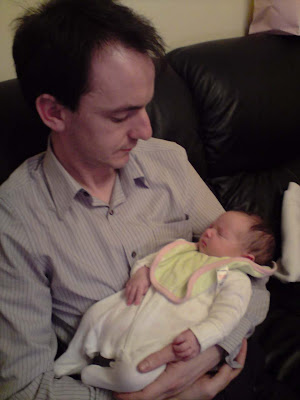 Picture of me with a tiny baby sleeping in my arms