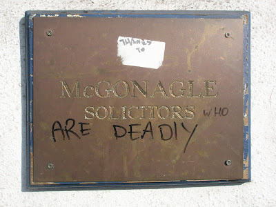 Plaque on wall for McGonagle solicitors with a sticker above it reading Thanks To, then the engraved McGonagle Solicitors, and underneath it has in black marker the words who are deadly - total text - thanks to McGonagle Solicitors who are deadly