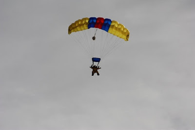 image shows a big multicoloured parachute with two people hanging out of it