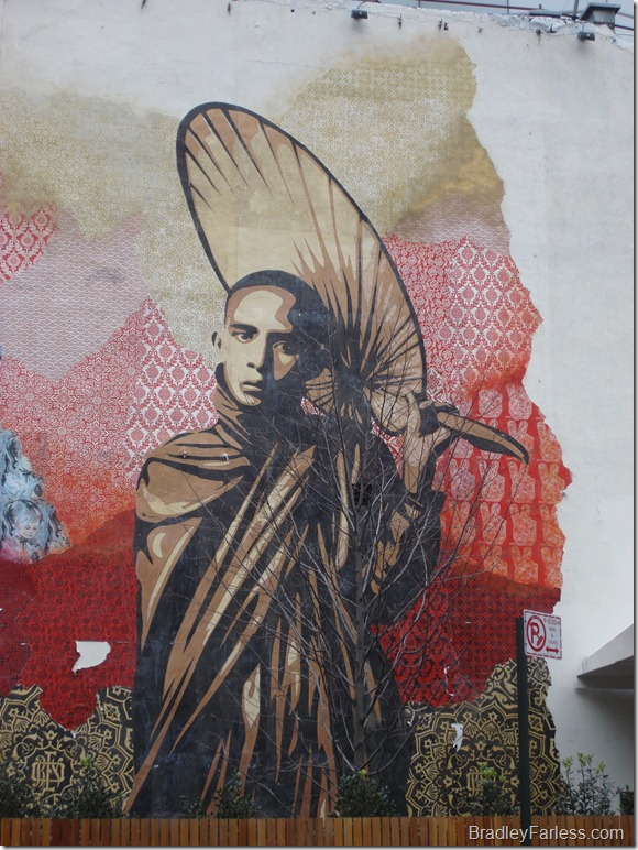 Wall mural of black man with fan and robe at 5th Street and Bowery, Manhattan.