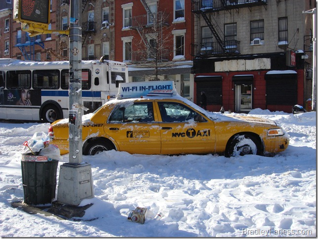 An abandoned taxi, left parked at an odd angle on the road becuase it was stuck in the snow.