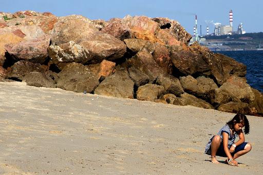 Jovem brinca na areia da praia de Albarquel