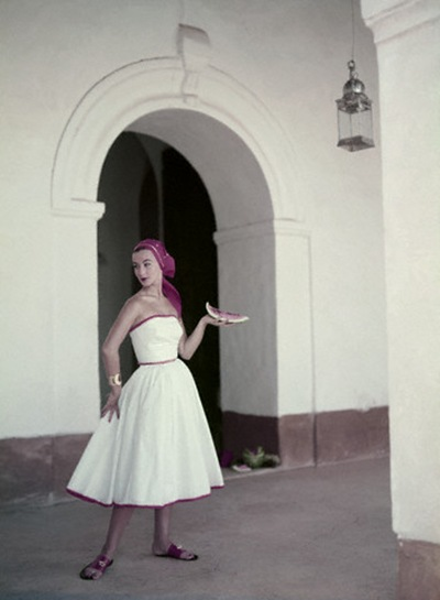 Model is wearing a strapless white cotton dress with a matching headkerchief, by Pat Premo and sandals by Bernardo 1953