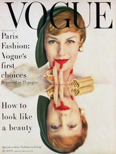 Model Mary Jane Russell's face with reflection on mirrored table top, in green hat with red lipstick and nails