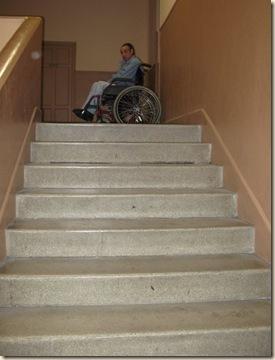 Escalera que da acceso al edificio que les ha sido concedido en cuya parte superior aparece Miguel en silla de ruedas, a quien Charo y otros compañeros tienen que subir y bajar a pulso cada vez que acude al centro