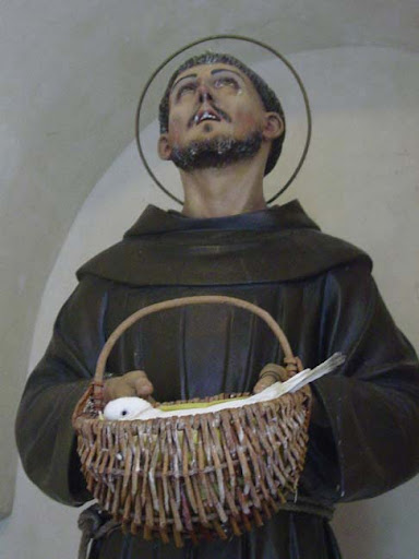 A statue of Francis with a live bird living inthe basket he holds