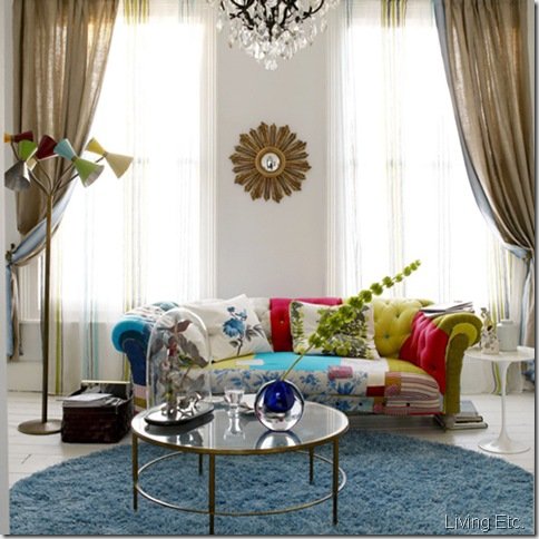 White living room unusual fun patchwork upholstered button chesterfield sofa round circular blue rug sash windows glass coffee table chandelier wallpaper feature wall chimney breast fireplace sunburst mirror 1960s standard floor lamp real home L etc 03/2008 not used