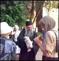 Father Irenaeus, handing out hot pies believers