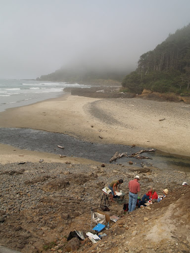 Artists on the beach that are painting the foggy coastline.