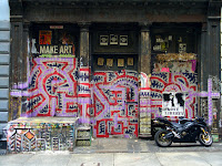 Soho, New York</p> <p>Graffiti appears in all places and is usually a sign of neglect and dereliction. The area was not derelict, or neglected. The building to either side are newly renovated. I took several shots of this building, setting up a tripod to make sure there was no hand jitter. After the third shot, this couple showed up, the guy basically ordering the girl to sit in the frame so he could take her picture. A very strange situation.</p> <p>Stuff like this happens all the time. People either do not understand why you are taking a picture, or want to get in on the act.  Too funny.