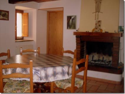 La sala da pranzo con il camino e dietro la cucina