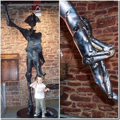 Statua del barone di Munchausen mentre fa gli scongiuri incrociando el dita